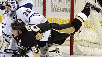 Penguins Sidney Crosby is airborne as he watches the play with Maple Leaf goalie Vesa Toskala at Mellon Arena.
