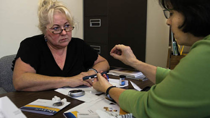 Joyce Tobias of Latrobe, left, newly diagnosed with diabetes, is instructed in how to use a blood sugar testing device by Sharlene Emerson, Diabetes Educator through UPMC.