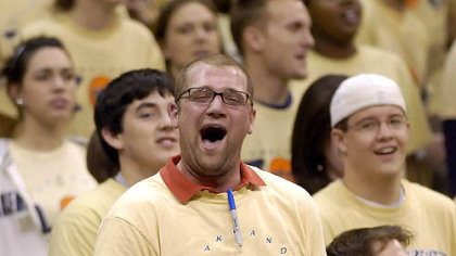 Ian Smith, president of the Oakland Zoo, cheers on the basketball team against Boston Tuesday.
