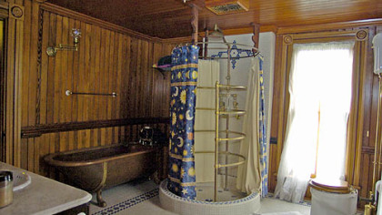 "One of the bathrooms features a copper clawfoot tub with carp ""legs"" and an open circular shower."