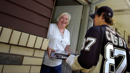 Pittsburgh Penguins team captaiin Sidney Crosby hand delivers tickets to season ticket holder Alice Kilgore.