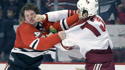 Daniel Carcillo, right, lands a punch on Chicago's Colin Fraser Friday on a night in which Carcillo logged 23 minutes of penalties.