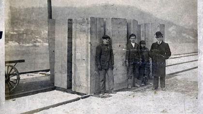 This photograph, taken on the banks of the Monongahela River, shows the arrival of rough box caskets in Fayette City, Fayette County, following the Naomi mine explosion. Robert R. Hawker, a 15-year-old wagoneer for the coal company, helped with the delivery and is second from right.