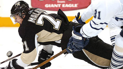 EvgenI Malkin is pulled down by the Maple Leafs' Pavel Kubina last night at Mellon Arena.