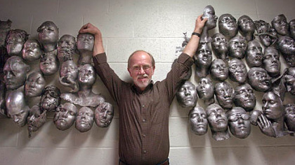 Carnegie Mellon University art professor Ron Bennett stands between some of the aluminum masks he and his sophomore art students have cast over the past 15 years in the basement of The University Center at Carnegie Mellon University.