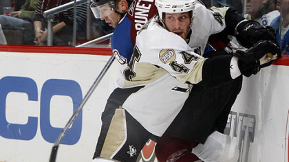 Penguins defenseman Brooks Orpik, front, pins Colorado Avalanche left winger Andrew Brunette to the boards while fighting for control of the puck in the first period last night's game in Denver.