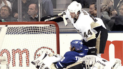 Penguins goalie Dany Sabourin, bottom, holds his head after a collision with the Maple Leafs' Darcy Tucker, center, as Brooks Orpik looks on in the first period Saturday in Toronto. Sabourin said he was not diagnosed with a concussion after the hit.