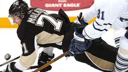 Penguins Evgeni Malkin is pulled down by the Leafs Pavel Kubina.