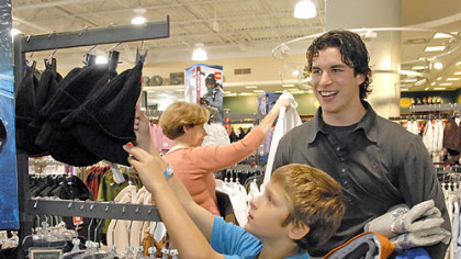 With shopping partner Penguins' forward Sidney Crosby in tow with his winter clothing selections, Austin Paterson, 10, shops for a winter hat during a Project Bundle-up shopping outing at Dick''s Sporting Goods in the Mall at Robinson yesterday.