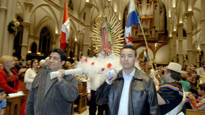 Ruben Ruiz, left, and Jose Arellano carry the statue of Our Lady of Guadalupe into St. Paul Cathedral in Oakland last night.