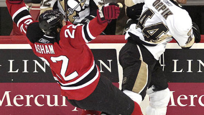 The Devils' Arron Asham, left, loses his balance after colliding with Brooks Orpik in the second period last night in Newark, N.J.