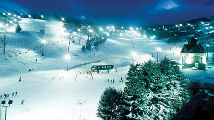 Bright lights and noisy snowmaking towers greet skiers and snowboarders as they head for the six-passenger Coco Cola Polar Bear Express lift at Seven Springs for an evening of fun on the slopes.