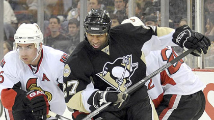 Penguins' Georges Laraque battles for a loose puck against Ottawa on Thursday. (12/13/2007)