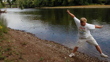 Russ Byars skips a stone at the Riverfront Park in Franklin, Venango County. Mr. Byars was recognized by Guinness World Records as the stone-skipping record holder with 51 skips.