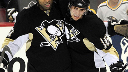 Penguins Georges Laraque congratulates teammate Erik Christensen after scoring against the Islanders in the first period last night.
