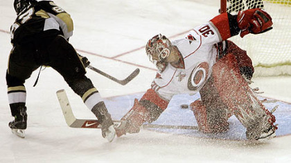 Sidney Crosby, left, scores on Carolina Hurricanes goalie Cam Ward in last night's shoot out.