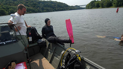 Eric Chapman, director of aquatic science, looks on diver Tamara Smith prepares to jump in, joining diver Jake Winkler already in the river.