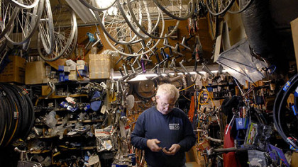 Jerry Kraynick sorts through some items as he creates space in his crowded Garfield bike shop last week for bicycles that will be donated to needy kids. Mr. Kraynick is co-director of The Bike Before Christmas program.