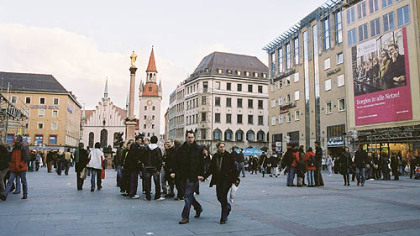 Bustling Marienplatz with its municipal buildings, offices and stores, is the center of Munich. A gilded statue of the Virgin Mary stands in the middle of the plaza. At one end is the old city hall, with its distinctive red roof.