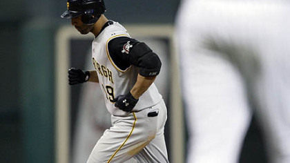 The Pirates' Jose Bautista, background, runs the bases after hitting a two-run home run off Houston Astros pitcher Chad Qualls, foreground, during the eighth inning of last night's game in Houston.