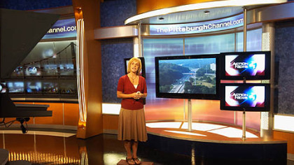 "Melanie Taylor, traffic reporter, rehearses in the reporter stand-up part of Channel 4's new set, an area that looks a little bit like the transporter pad from ""Star Trek."""