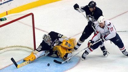Penguins goalie Marc-Andre Fleury, left, makes a save on a shot by Washington Capitals' Chris Clark (17) as Penguins' Ryan Whitney looks on during the third period last night.